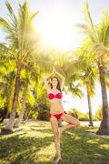 Portrait of young woman wearing bikini standing on one leg under palm trees - stock photo