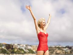 Woman wearing red one piece swimsuit standing on beach with arms raised - stock photo