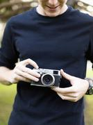 Stock Photo of Young man holding camera