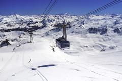 cableway to transport large numbers of people high in mountains of french alp - stock photo