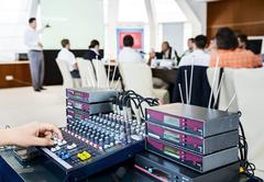 Equipment for wireless microphones and man adjusts the volume on mixing conso Stock Photos