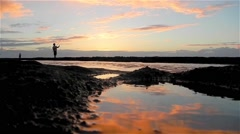 Two Men Fishing on Beach, Reflection of Sunrise Stock Footage