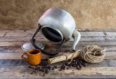 old kettle,paper roll,rope reel and coffee beans on wooden background - stock photo