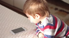 Little boy with soother takes a white cellphone and walks away with it Stock Footage