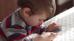 Close up little boy using white telephone with touch screen Stock Footage