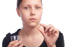 teen girl with pill and water  in glass - stock photo