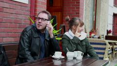 Man sitting with his girl friend in outdoor cafe receives a phone call Stock Footage