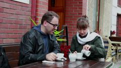 Young couple have a coffee time at the sidewalk cafe Stock Footage