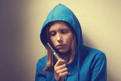 dark portrait of a junk teen girl with syringe - stock photo
