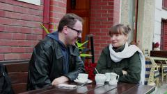 Happy couple have a good laugh while sitting in outdoor cafe and drinking coffee Stock Footage