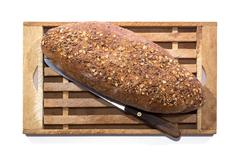 whole grain bread and vintage knife on wooden cutting board over white - stock photo