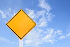yellow traffic sign isolated on blue sky - stock photo