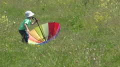 Sweet little boy walking with colored umbrella in spring blossom field 4K Stock Footage