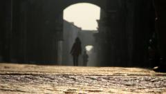 Tourists walking on ancient stone road in the morning sunlight Stock Footage
