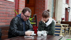 Troubled couple sitting in silence in courtyard cafe  Stock Footage