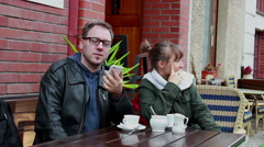 Man talking on the phone and to his girl friend sitting next to him Stock Footage
