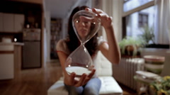 Woman holding an hour glass in her apartment Stock Footage
