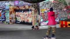 Boy skating past graffiti, Southbank, London - stock footage