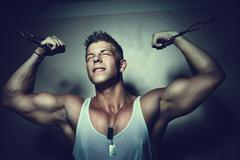 guy trains his pecs using crossover - stock photo