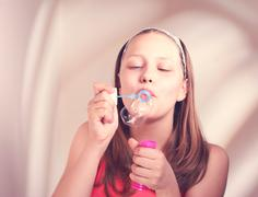 happy teen girl blowing soap bubbles - stock photo