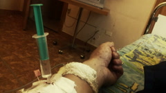 Hand of sick person with syringe and drip Stock Footage
