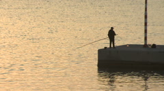Greece, Naxos, Single Fisherman with Pole on Dock Stock Footage