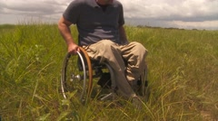 Paraplegic man moving with his wheelchair in the grass in daytime Stock Footage