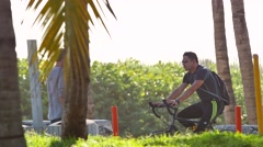Man riding his bike on the beach Stock Footage