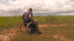 Handicapped white man trying to move on the plain with his wheelchair Stock Footage