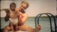 1645 - young mother with baby at lake - vintage film home movie Stock Footage