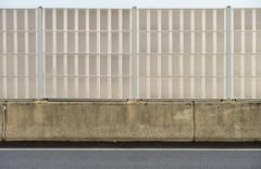 Noise barrier wall beside the highway Stock Photos