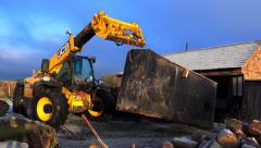 Building construction - jcb tractor loader lifting large scrap metal tank Stock Footage