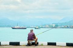 fisherman fishing in the port - stock photo