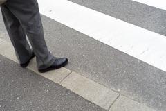 Man legs in slag pants waiting to cross the street at a crosswalk Stock Photos