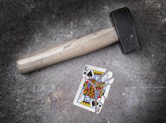 Hammer with a broken card, king of spades Stock Photos