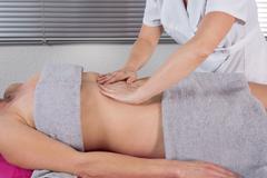Young woman having stomach ayurveda spa treatment. Stock Photos