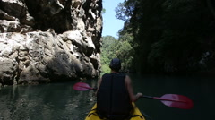 Man rowing kayak and floats along the gorge Stock Footage