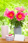 Pink peonies in metal vase, gift and empty card for letter - stock photo
