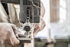 Blurred motion of carpenter working, preparing door for hinges Stock Photos