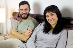 Stock Photo of smiling young couple in bed looking