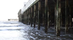 Waves Roll Up Against the Piles or Pillars of a Pier Stock Footage