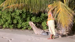 Hawaii dancer standing behind palm leaves and waving a greeting Stock Footage
