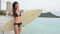 Surfer girl surfing showing mahalo shaka hand sign on Waikiki Beach Arkistovideo