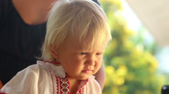Baby girl in embroidery dress watching cartoon closeup Stock Footage
