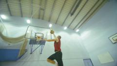 Basketball player dribbles the ball and slam dunks Stock Footage