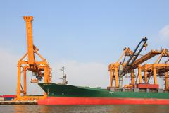 Commercial ship on port  with big loading crane Stock Photos