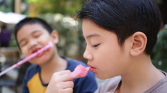 Young asian boys sitting near attractions. Stock Footage
