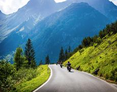 Moto racers on mountainous road Stock Photos