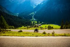 motorcyclist on mountainous highway - stock photo