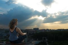 Girl meditating at sunbeam - stock photo